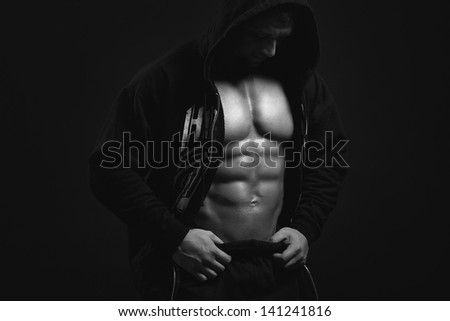 black and white strong man in the hood showing his press on blac - stock photo