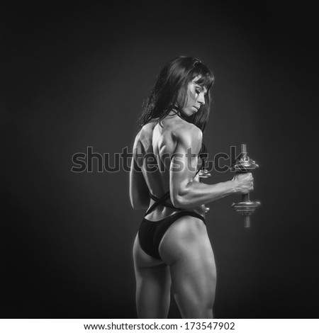 black and white strong sexy girl is training with dumbbells on black