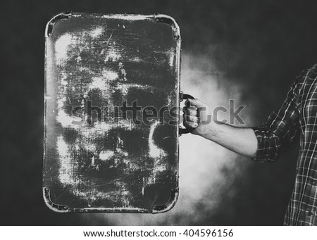black and white studio image of a man holding an old suitcase - stock photo