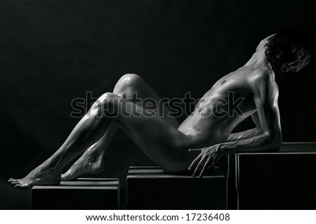 Black-and-white studio portrait of a young muscular naked man - stock photo