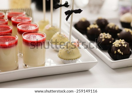 Black and white sweet table with hand made pralines, cake pops and strawberry panna cotta at an elegant wedding reception. Shot in natural light, shallow DOF, subtle grain and toning. - stock photo