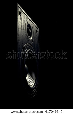 black and white toned image of an audio speaker isolated on a black background - stock photo