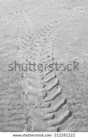 Black and white tractor tire tracks on beach sand - stock photo