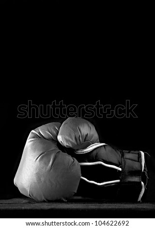 Black and white used boxing glove on black - stock photo