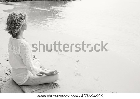 Black and white view of a mature woman in holiday destination beach contemplating the sea sitting in yoga position, meditating outdoors. Well being mature sport healthy lifestyle, nature exterior. - stock photo
