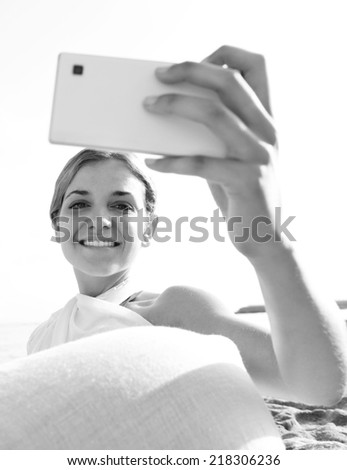 Black and white view of attractive tourist woman relaxing on sandy beach by the sea, holding a smartphone device taking selfies pictures of herself, networking on holiday. People technology outdoors.