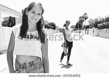 Black and white view of two diverse teenagers friends smiling with skateboards, sporty and skating on a suburban street outdoors. Adolescent girls enjoying time together, lifestyle sport activities. - stock photo