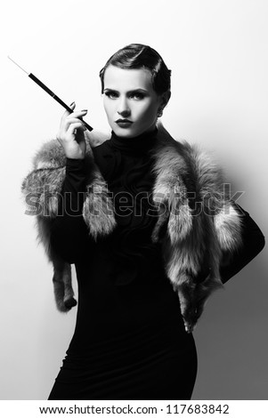 Black and white vintage image of beautiful woman with cigarette - stock photo