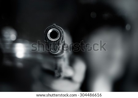 Black and white, woman pointing a old gun to front with one Hand on dark background - stock photo