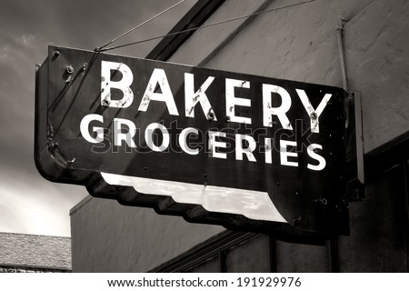 Black and White Worn Bakery and Groceries Sign in Small Town - stock photo