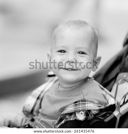 Black and white, 1 year baby sitting in the baby carriage, blonde, plaid shirt, jeans, a city on the background of trees. - stock photo