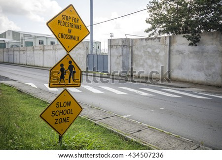 Black and yellow children crossing ahead sign in the street of Road Town, Tortola