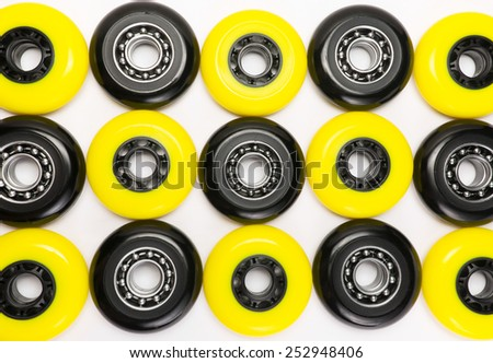 Black and yellow color inline skate wheels laying on white background - stock photo