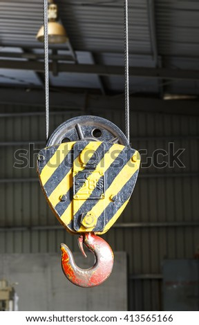 Black and yellow cranes hooks hanging on steel in factory - stock photo