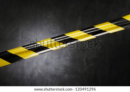 Black and yellow plastic barrier tape blocking the way. - stock photo