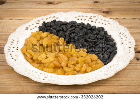 Black and yellow raisins on the wooden backgrounds. - stock photo