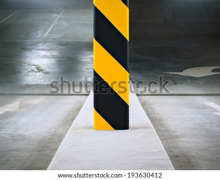 Black and yellow striped column at the entrance to an underground parking garage. - stock photo