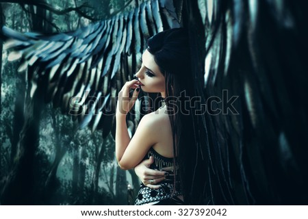 Black Angel. Pretty girl-demon with black wings. An image for Halloween. Image of an old book of fairy tales. Fashionable toning with noise - stock photo