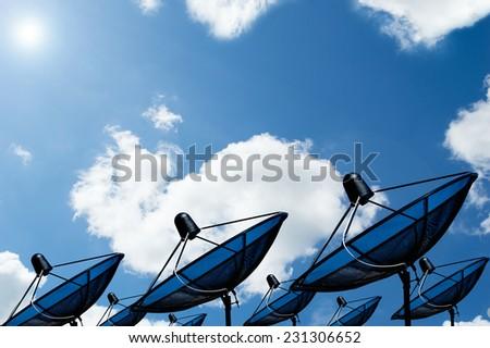 black antenna communication satellite dish on blue sky - stock photo