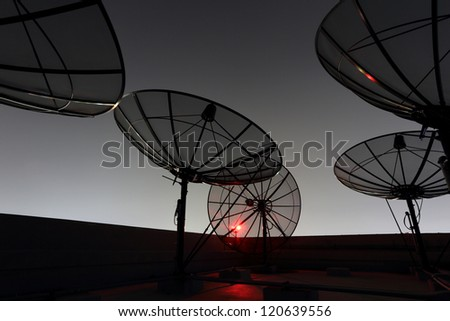 black antenna communication satellite dish over twilight sky in cityscape - stock photo