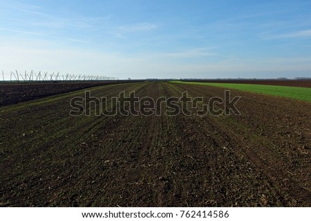 black arable land with blue sky in the background