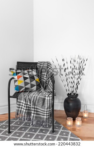 Black armchair, lanterns and decorations in the living room. - stock photo