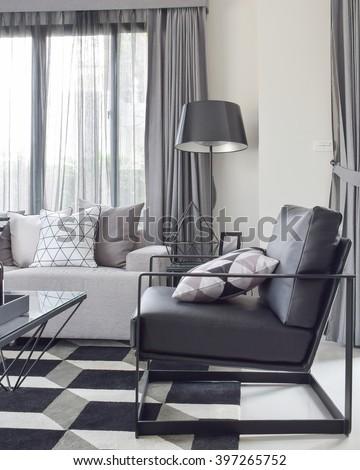 Black armchair with geometric rug in modern living corner - stock photo