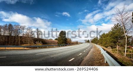 black asphalt road on sunny spring day - stock photo