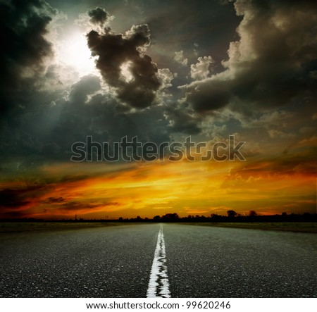 black asphalt road with arrow to sunset - stock photo