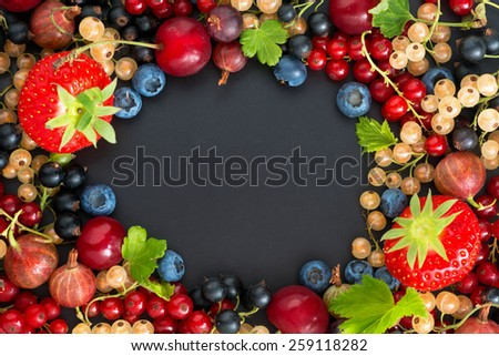 black background for text with fresh garden berries, horizontal, top view - stock photo
