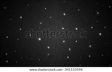 black background with a scattering of diamonds - stock photo