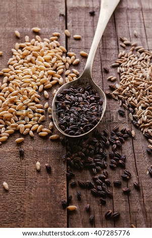 Black barley, wheat and rye grains over rustic wooden background