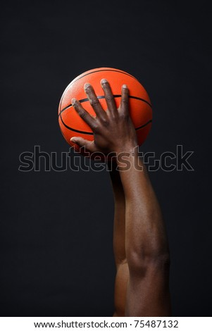 Black basketball player with red shirt and blue shorts holding basketball.