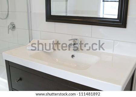 Black bathroom vanity and mirror in a contemporary bathroom - stock photo