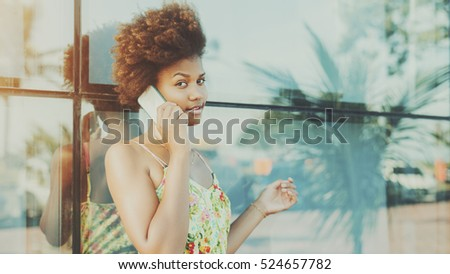 Black beautiful attractive young brazilian teen girl with curly hair in dress, talking on smartphone standing in front of tiled glass wall with reflections of palms and cars, sunny summer day