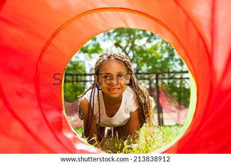 Black beautiful girl crawling though the tube - stock photo