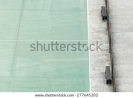 Black bench beside the basketball field in the urban park. - stock photo