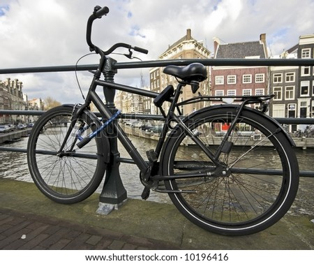 Black bike chained at the bridge from an Amsterdam canal in the Netherlands - stock photo