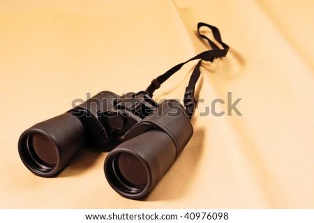 Black binoculars on ancient parchment paper - stock photo