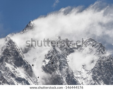 Black birds and snow flags on the top of the Lhotse (8516 m) - Mt. Everest region, Nepal - stock photo