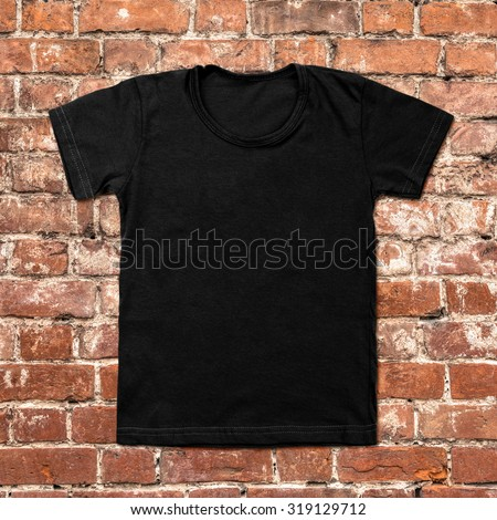 Black blank t-shirt on dark brick background. - stock photo