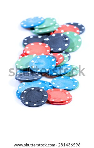 Black, blue, green and red poker chips in a group on a white background. - stock photo
