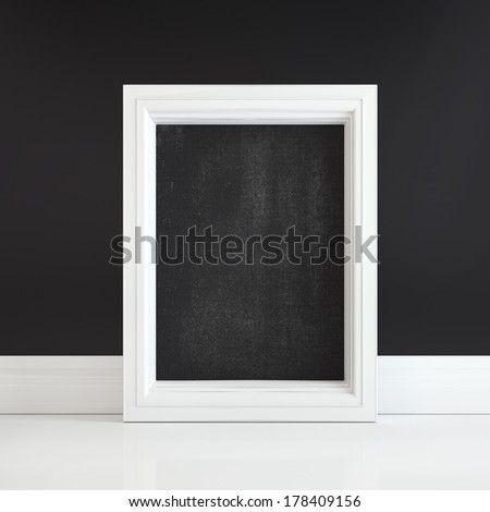 Black board in white frame on a white floor near black wall - stock photo