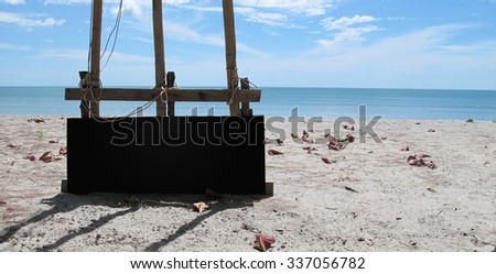 Black board on the ground with the sea behind. And wither leaf. - stock photo