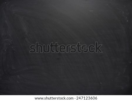 Black board with the traces of chalk over its surface as a background texture - stock photo