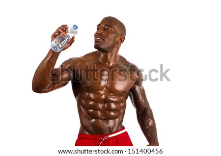 Black bodybuilder drinking water after a hard workout.  Strong man with perfect abs, shoulders,biceps, triceps and chest. Isolated on white background - stock photo