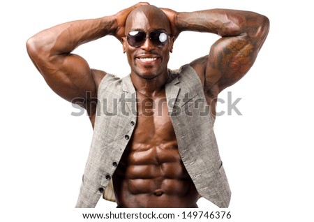 Black bodybuilder smiling wearing a vest and sunglasses.Strong man with perfect abs, shoulders,biceps, triceps and chest. Isolated on white background