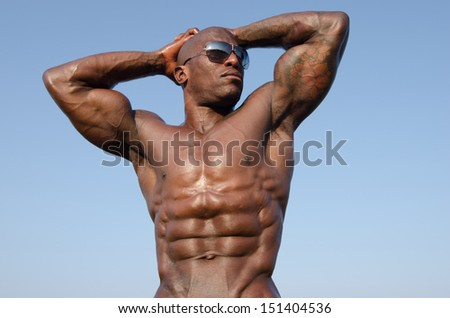 Black bodybuilder wearing sunglasses showing off his muscles on a sky background. Strong man with perfect abs, shoulders,biceps, triceps and chest. Isolated on white background - stock photo
