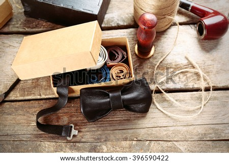 Black bow tie and full cardboard gift box of ties on wooden table, close up - stock photo