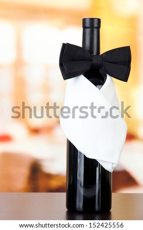 Black bow tie on wine bottle on bright background